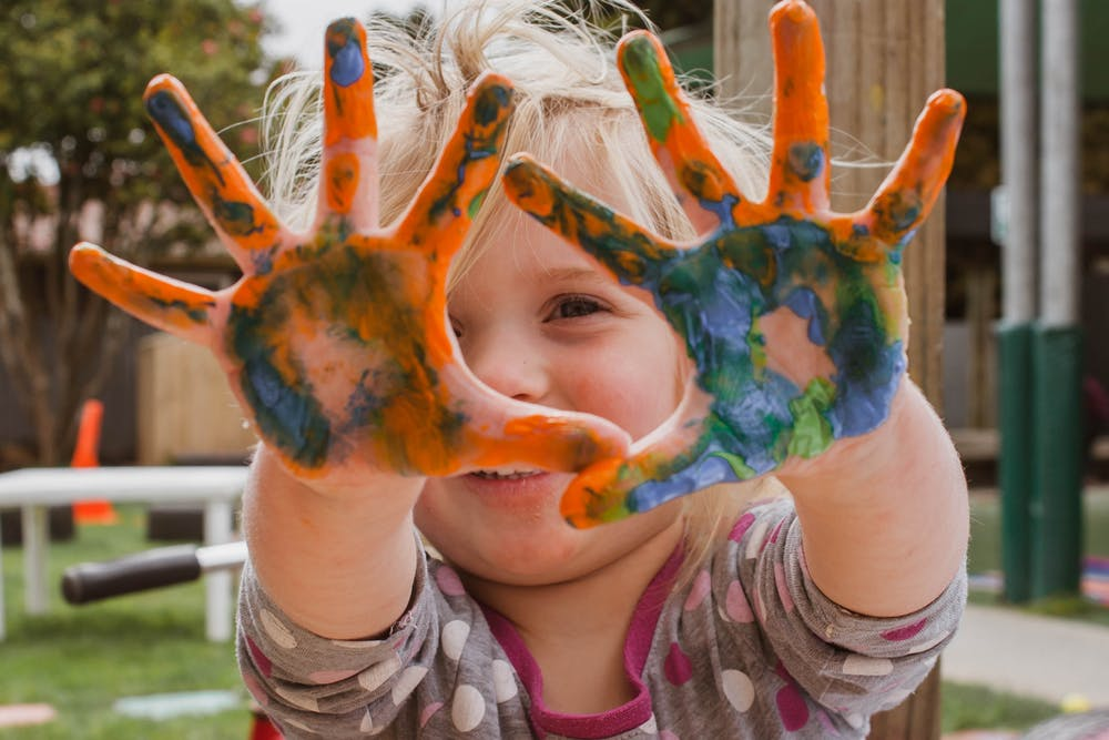 child with paints in her hands